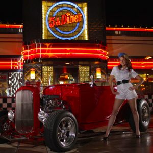 woman stands in front of hot rod outside 5 and Diner